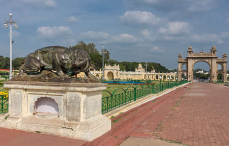 Mysore, India - October 27, 2013: Combination of brown East gate and dark brown bronze statue of aggressive lioness in front garden of Mysore Palace under cloudscape. Editorial