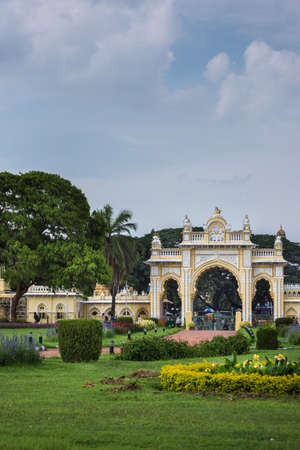 Mysore, India - October 27, 2013: Green garden with flowers in front of closed North Gate to Mysore Palace under cloudscape.