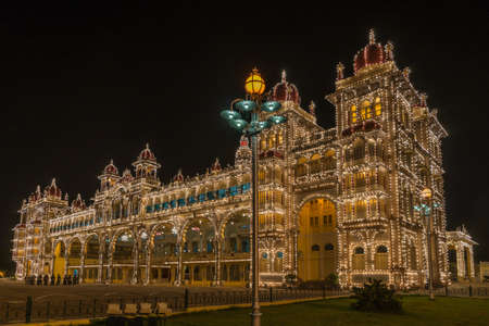 Mysore, India - October 27, 2013: Sound and light show illuminates Mysore Palace when dark late evening. Frontal view shot from Northeast corner. Music band in photo.