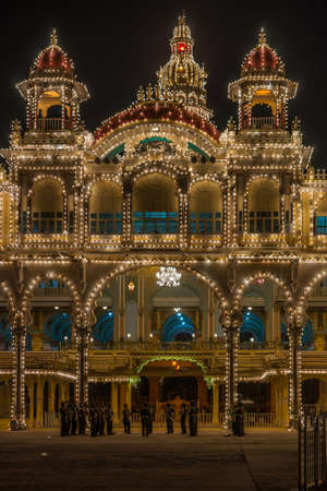 Mysore, India - October 27, 2013: Frontal shot of East facade center of Mysore Palace at nightly Sound and Light show. Beige building with towers and maroon domes. Central tower with golden domes. Music band.