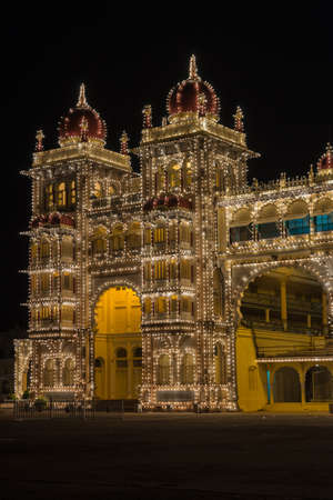 Mysore, India - October 27, 2013: Southeast corner towers of Mysore Palace at nightly Sound and Light show. Beige building with towers and maroon domes. Hundreds of lights.