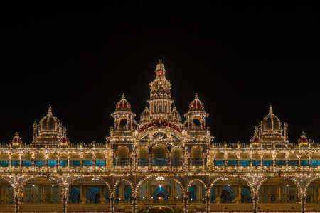 Mysore, India - October 27, 2013: Upper level with towers and domes of facade center of Mysore Palace at nightly Sound and Light show. Beige building with towers and maroon domes. Hundreds of lights.