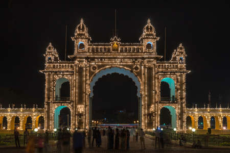 Mysore, India - October 27, 2013: Main East gate of Mysore Palace illuminated at nightly Sound and Light show. Beige building with towers and maroon domes. Hundreds of lights. Seen from inside domain.