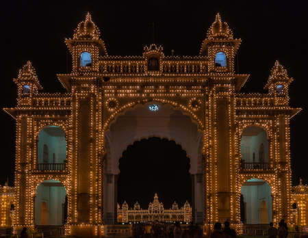 Mysore, India - October 27, 2013: Main East gate of Mysore Palace illuminated at nightly Sound and Light show. Palace self visible through gate. Hundreds of lights. Seen from outside domain.