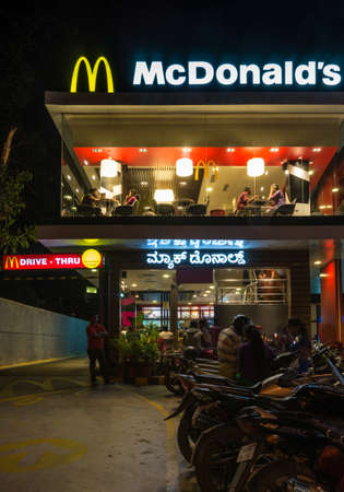 Mysore, India - October 27, 2013: Illuminated Mcdonalds Restaurant at night on intersection of JLB Road and Dhanavantri Road. Row of motorcycles and guests outside and inside.