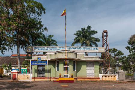 Mysore, India - October 28, 2013: Green entrance guard building with State red and yellow flag of historic Karnataka Soap and Detergents factory under blue sky and with green trees .
