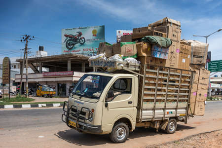 Mysore, India - October 28, 2013: Beige extremely overloaded parked delivery van along Hunsur Road under blue sky. Street scene with billboards and business buildings.