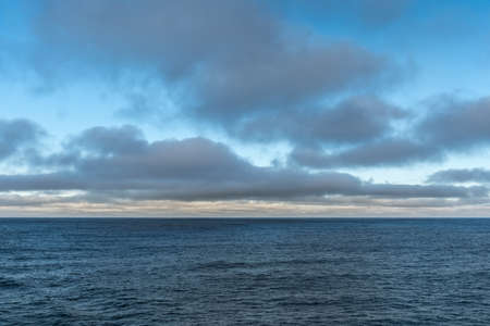 Tasman Sea, Australia - March 20, 2017: Lower third of photo is blue sea water with low hanging brown clouds on the horizon and higher floating gray clouds. Dispersed blue patches of sky.