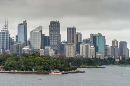 Sydney, Australia - March 21, 2017: Green trees of Botanical garden in front of city skyline section under gray sky. Shot from the bay: people on shore line, boats and buoys. Banco de Imagens - 86659586