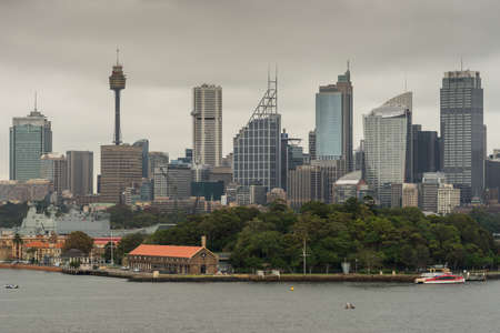 Sydney, Australia - March 21, 2017: Green trees of Garden Island in front of city skyline section with Eye tower under gray sky. Shot from the bay: people on shore line, boats and buoys.