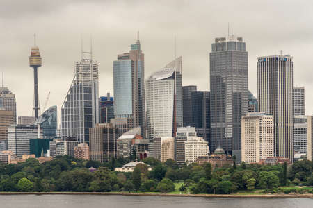 Sydney, Australia - March 21, 2017: Green trees of Botanical garden in front of city skyline section under gray sky. Shot from the bay: people on shore line and Sydney Eye tower. Editorial
