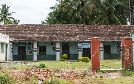 Chikunda, India - October 28, 2013: The pastel painted Muslim primary school of the village features a tiled saddle roof, and messages in Urdu,  Arabic and Kannada language. Indian national flag on pillars. Green vegetation. Editorial