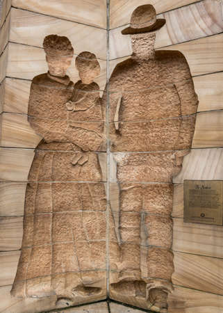 Sydney, Australia - March 22, 2017: Closeup of The Settlers side of three facetted First Impressions Monument at Playfair Street. Beige structure with edges silhouettes of man, woman and child.