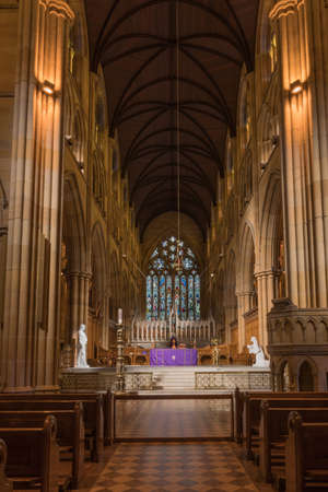 tabernacle: Sydney, Australia - March 23, 2017: Chancel with purple-dressed altar, gothic tabernacle, white statues, and large stained window in back. Rather dark alcove like setting. Benches and pulpit in front. Editorial