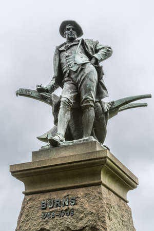 Sydney, Australia - March 23, 2017: Closeup of figure on top of pedestal, an all bronze statue of Robert Burns on side of Vernon building of Art Gallery of NSW. Against silver sky.