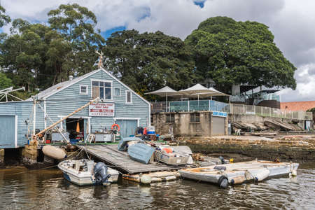 trashy: Sydney, Australia - March 24, 2017: Wooden blue-painted Abbotsford boat repair and storage shop on shore with slipway along Parramatta River. Trashy boatyard with tools, sloops, workbench and more.