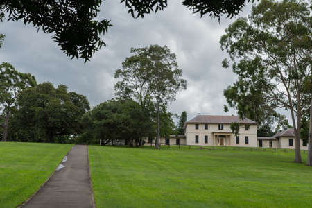 Parramatta, Australia - March 24, 2017: Beige, two-level colonial Government House in Domain park under heavy rainy sky. Green trees and lawn.