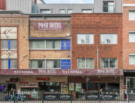 Sydney, Australia - March 25, 2017: Historic brich Posh Hotel with retail businesses on street level on Broadway in Railway Station neighborhood. Pedestrians and advertisements, images of fishing.