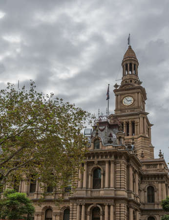 Sydney, Australia - March 25, 2017: View on corner of brown stone historic monumental Town Hall with clock tower under heavy sky and tree in foreground. Editorial