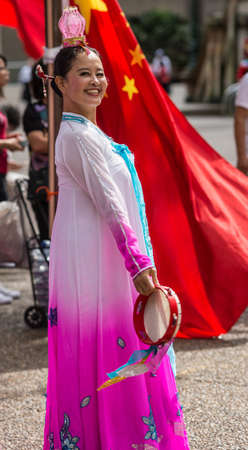 Sydney, Australia - March 25, 2017: Chinese woman living in Australia welcomes Chinese Premier Li Kequing with traditional dances, songs and music. Pink dress. Red flag. Public square side of Town Hall.