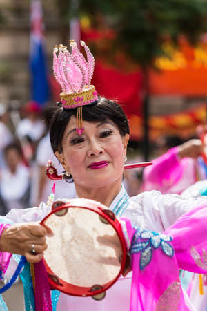 presence: Sydney, Australia - March 25, 2017: Chinese woman living in Australia welcomes Chinese Premier Li Kequing with traditional dances, songs and music. Pink dress. Public square side of Town Hall.