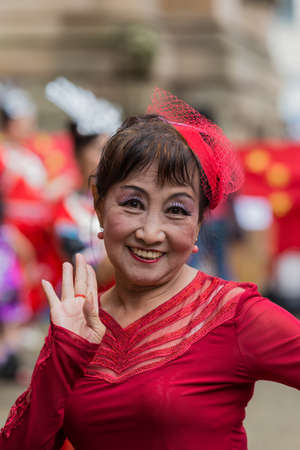 presence: Sydney, Australia - March 25, 2017: Head shot of Chinese woman living in Australia welcomes Chinese Premier Li Kequing with traditional dances, songs and music. Public square side of Town Hall.