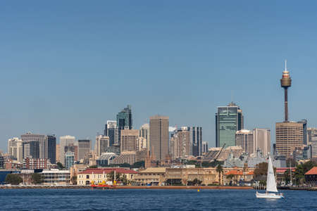 Sydney, Australia - March 26, 2017: Closeup kind of shot of selection of tall office towers skyline seen off the water under blue sky. White sail boat, Navy ship and spires of Saint Mary Cathedral. Publikacyjne