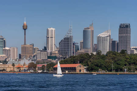 Sydney, Australia - March 26, 2017: Closeup kind of shot of selection of tall office towers skyline seen off the water under blue sky. White sail boat, Navy ship.