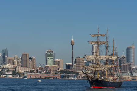 Sydney, Australia - March 26, 2017: Sailing tall black and red ship with downtown skyline in background on blue water and under clear skies.