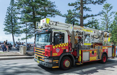 Sydney, Australia - March 26, 2017: Red, yellow and white fire truck with ladder and pump motors on South Steyne along boardwalk. Green trees and people.