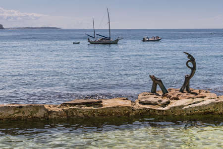 Sydney, Australië - 26 maart, 2017: Oceanides-standbeeld op rots in Overzees Tasman voor Mannelijk strand door Helen Leele. Twee kleine boten nutteloos in water. Redactioneel