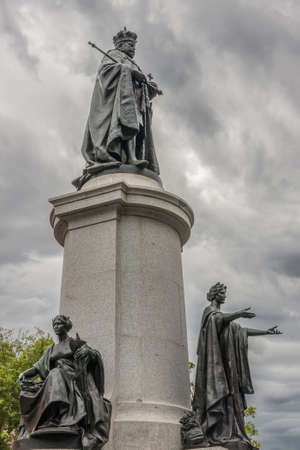 Adelaide SA, Australia - November 20, 2009: Monumental statue of King Edward VII in full coronation regalia under heavy cloudscape on pedestal with two female statues at foot. Green foliage.
