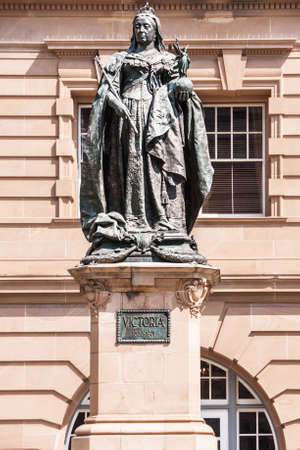 Brisbane, Australia - December 8, 2009: Closeup of Queen Victoria statue in full coronation regalia in Queens Gardens in front of historic brown stone Land Administration Building.