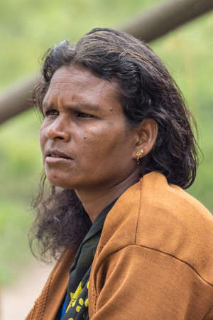 Coorg, India - October 29, 2013: Dubare Elephant Camp. Protrait of adult youg woman with long black hair, ochre vest and golden earring staring in distance.