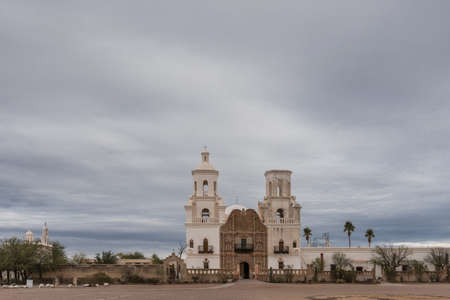 Tucson, Arizona, USA - January 9, 2018: Wide view on White and brown front facade of Historic San Xavier Del Bac Mission under heavy gray, white cloud deck. Some greenish desert plants in front. Editorial