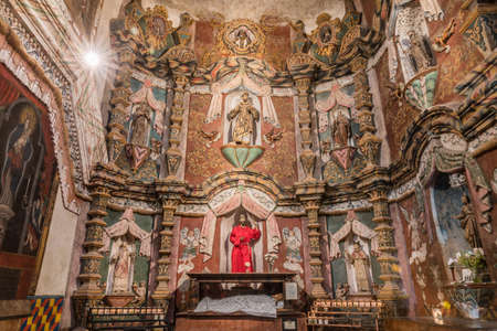 Tucson, Arizona, USA - January 9, 2018: West Transept reredos inside historic San Xavier Del Bac Mission. Many saint statues of which San Francisco is the main. Editorial