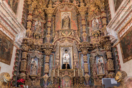 Tucson, Arizona, USA - January 9, 2018: Main altar with massive reredos inside historic San Xavier Del Bac Mission. Many saint statues, paintings, tabernacle, candles.