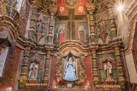 Tucson, Arizona, USA - January 9, 2018: East Transept reredos inside historic San Xavier Del Bac Mission. Many saint statues, carvings and frescoes of which the virign Mary is the main. Editorial
