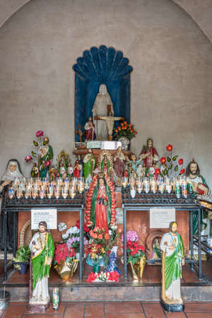 Tucson, Arizona, USA - January 9, 2018: Altar inside side chapel for Virgin of Guadalupe at historic San Xavier Del Bac Mission. Many different saint statues and an abundance of lighted candles. Some flowers.