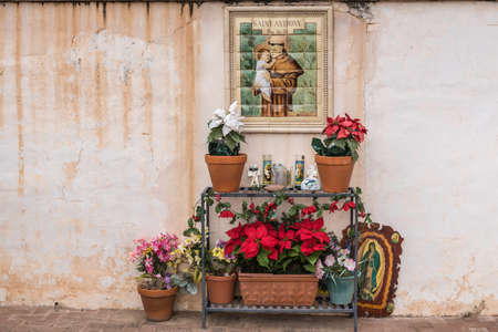 Tucson, Arizona, USA - January 9, 2018: Outside stained tile mural of Saint Anthony at historic San Xavier Del Bac Mission. Table with many flowers and candles in front. Editorial