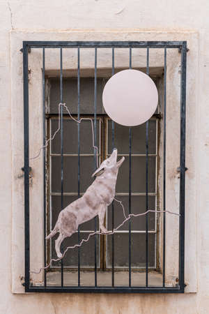 Tucson, Arizona, USA - January 9, 2018: Closeup of outside metal window enclosure artwork of wolf howling to moon at historic San Xavier Del Bac Mission. Window fence.