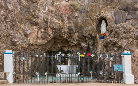 Tucson, Arizona, USA - January 9, 2018: Grotto in rocks with statues of Mary and Bernadette outside historic San Xavier Del Bac mission. Window fence. Flowers and fence.