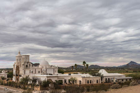 Tucson, Arizona, USA - January 9, 2018: The territory and entire complex of historic San Xavier Del Bac mission under heavy gray low hanging cloudscape. Landscape with hills in distance. Editorial