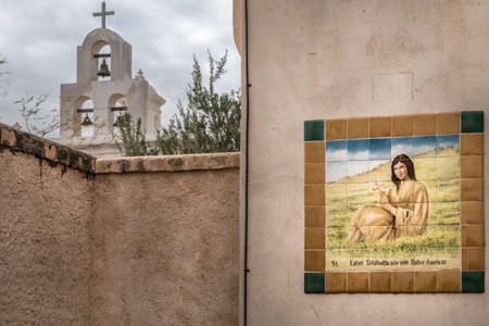 Tucson, Arizona, USA - January 9, 2018: Outside stained tile mural of Saint Kateri Tekakwitha at historic San Xavier Del Bac Mission. Young Indian woman on green-yellow lawn. Bell tower in back. Editorial