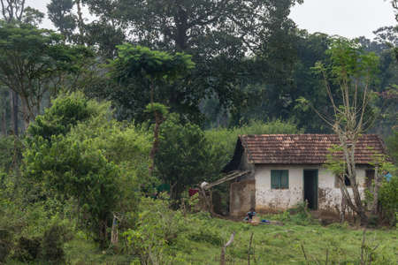 Coorg, India - October 29, 2013: Dubare Elephant Camp. Small Family stone house with panes as roof. Green jungle setting under gray sky. Woman doing laundry in front.