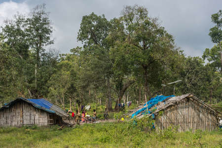 Coorg, India - October 29, 2013: Dubare Elephant Camp. Two family dwellings are long bamboo-clay huts with blue tarp as roof. Green jungle setting under gray sky. A few tribal people hang around.