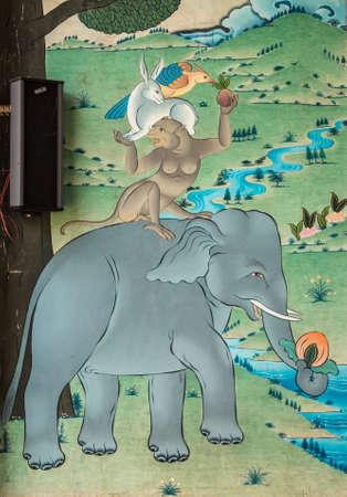 Coorg, India - October 29, 2013: Outside wall painting under Mandapam  Padmasambhava Vihara at Namdroling Buddhist Monastery. Tower of elephant, monkey, rabbit, bird. Editorial