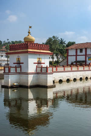 Madikeri, India - October 31, 2013: Shree Omkareshwara Temple. White, golden and marron Shrine set in and reflected in the pond under blue sky. Editorial