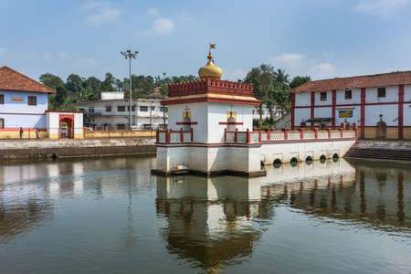 Madikeri, India - October 31, 2013: Shree Omkareshwara Temple. White, golden and marron Shrine set in and reflected in the pond under blue sky. Stock Photo