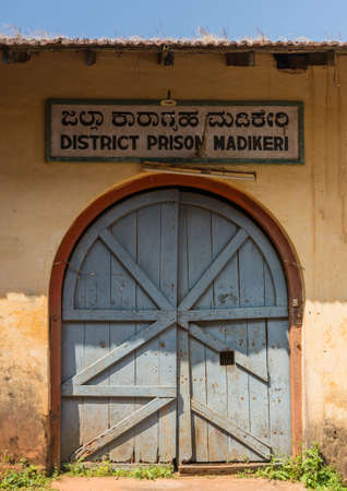 Madikeri, India - October 31, 2013: Closeup of the wooden, blue-gray entrance door to District Prison. Framed in yellow dirty wall. Sign with TL-Lamp. Weed on roof, blue sky. Editorial